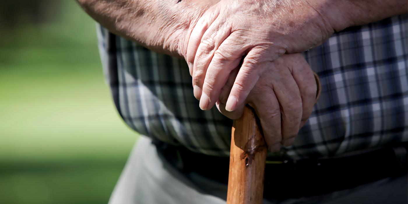 elderly man leaning on cane