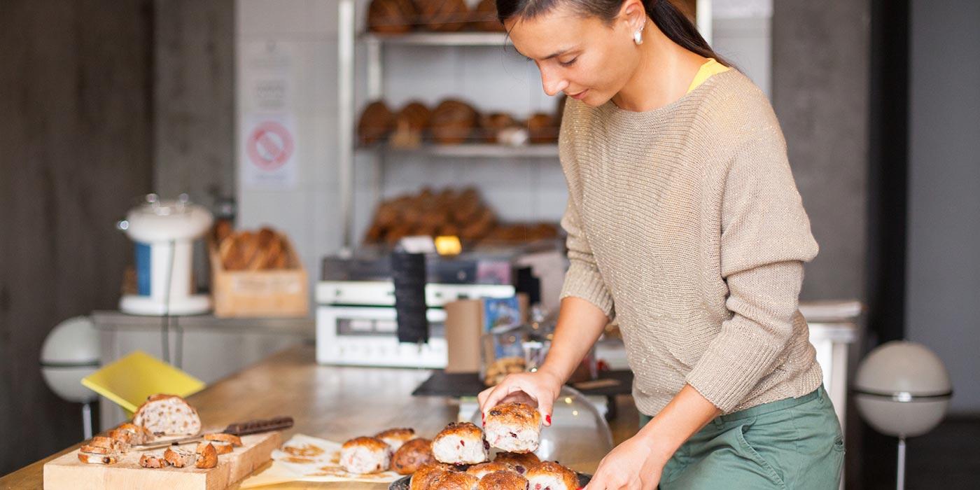 woman cutting bread in kitchen