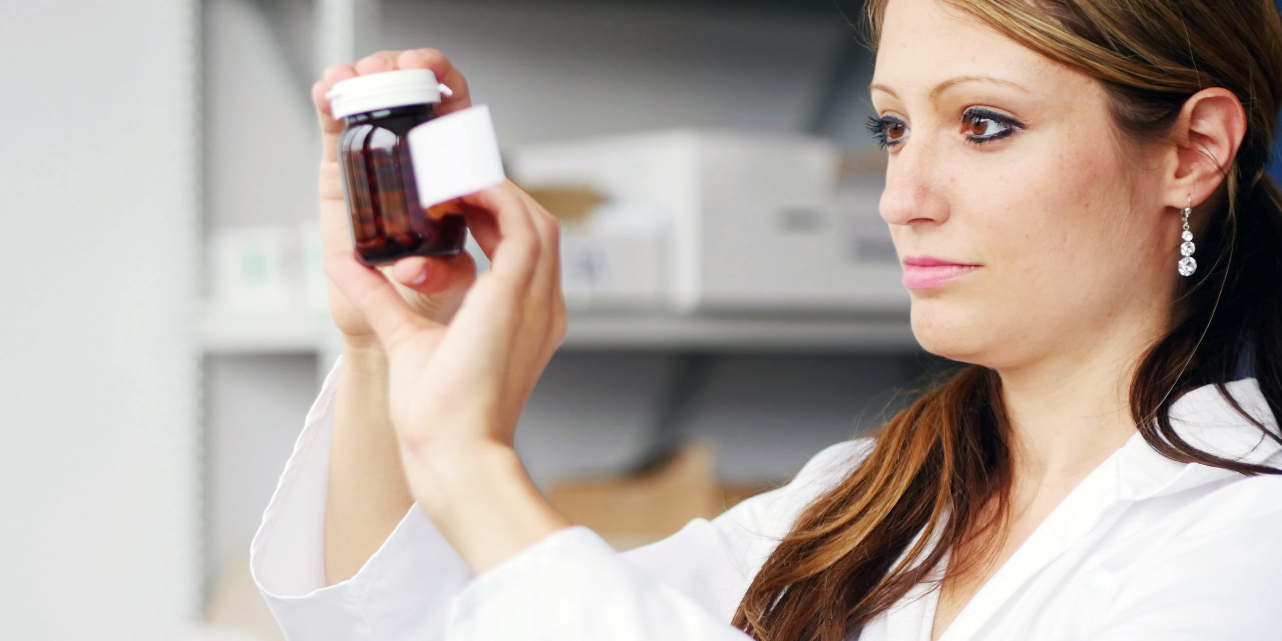 Pharmacist looking at medicine bottle