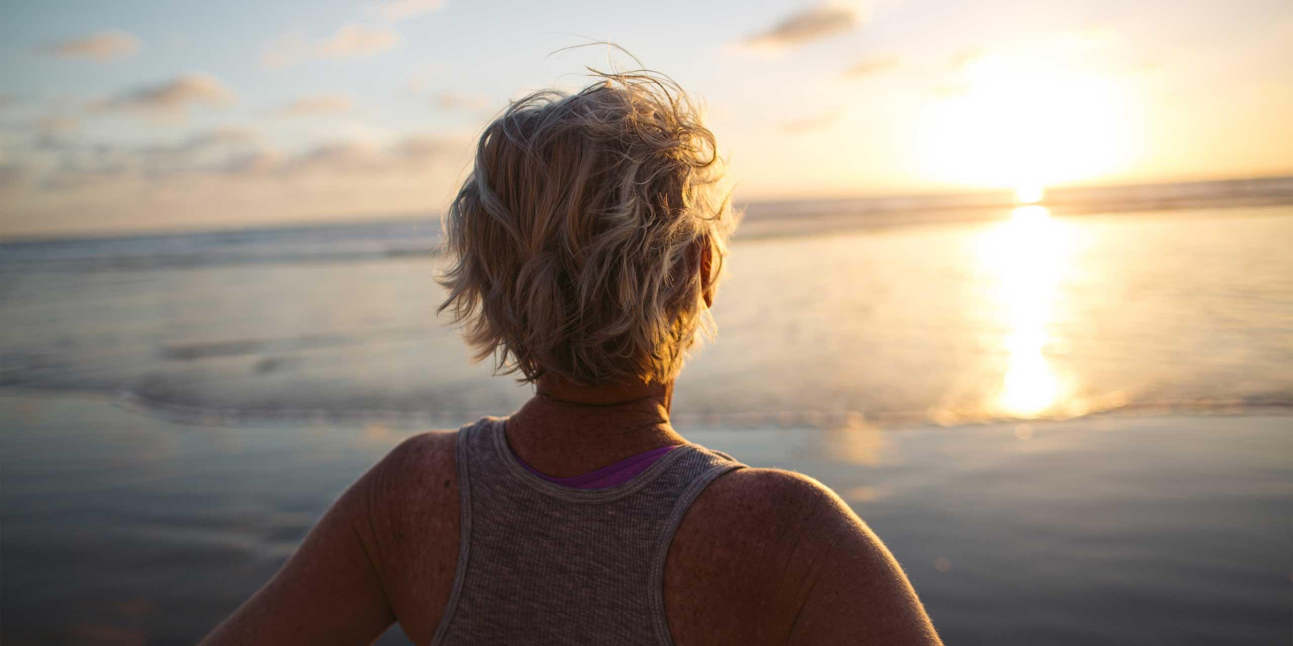 Women looking at sun over ocean
