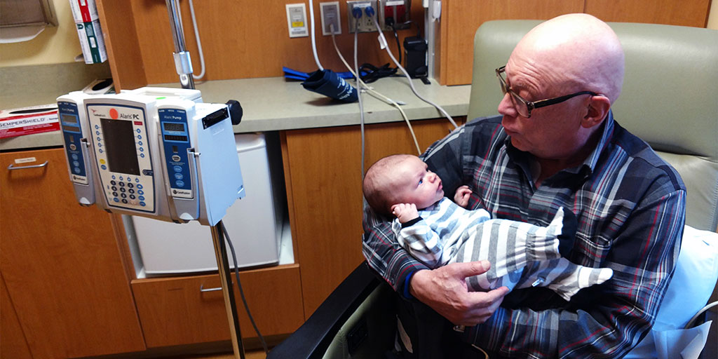 MARK FISHMAN HOLDS HIS NEWBORN GRANDSON WHILE RECEIVING CHEMOTHERAPY TREATMENT FOR HIS PANCREATIC CANCER.