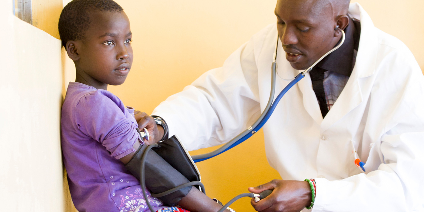 doctor listening to boy's heart in developing nation