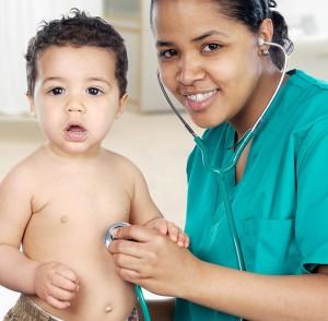 Enfermera escuchando el corazón del niño