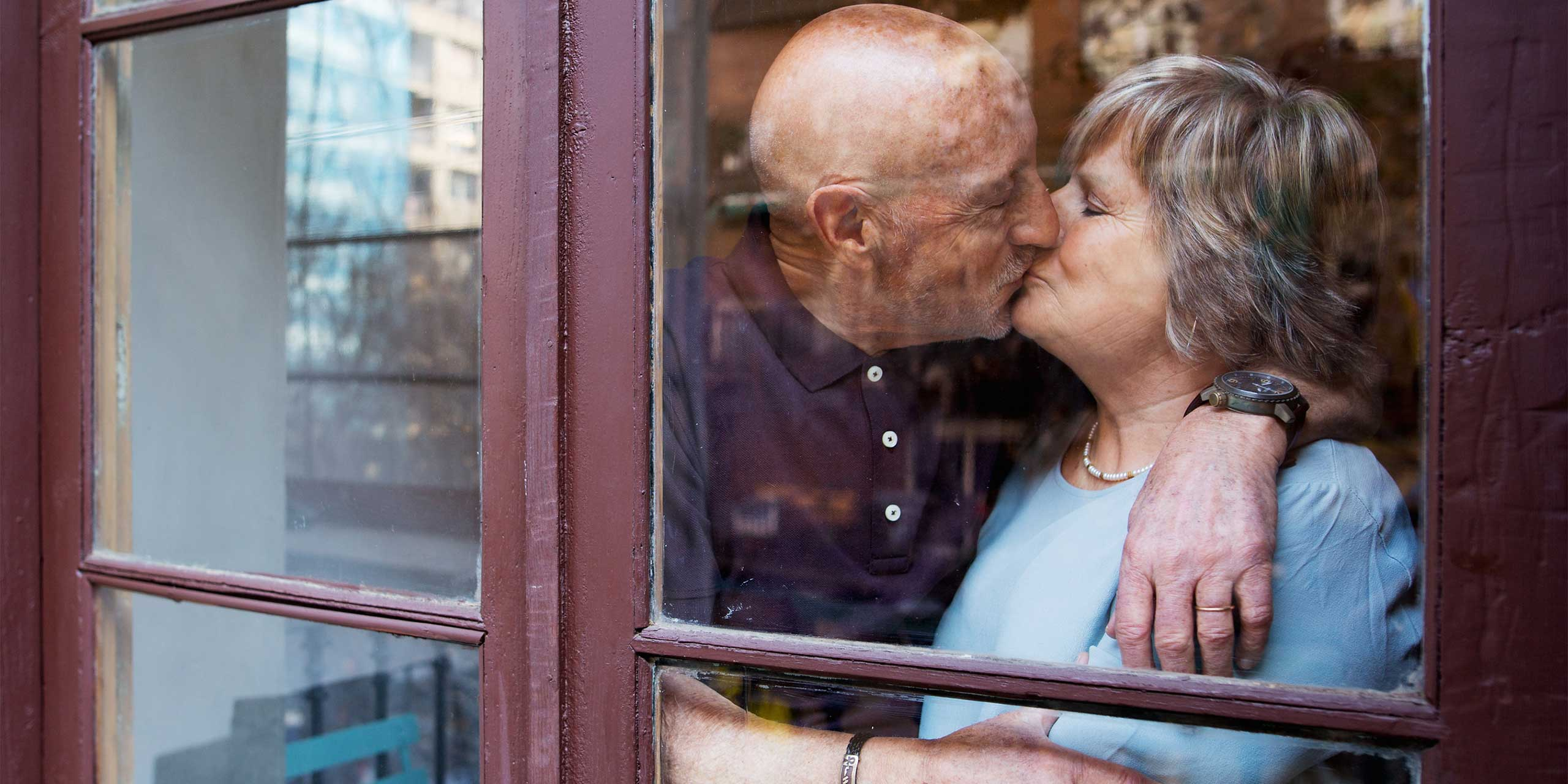 husband and wife kissing by window